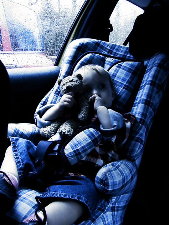 baby boy sitting in a plaid booster seat