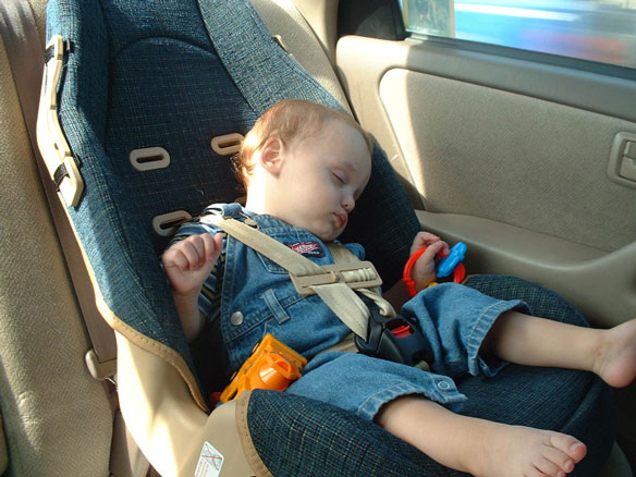 small child sleeping in a booster seat