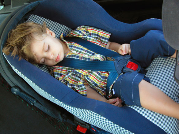sleeping child fastened into a car booster seat