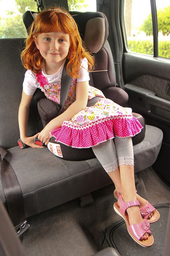 child clicking her seatbelt while sitting in a booster seat
