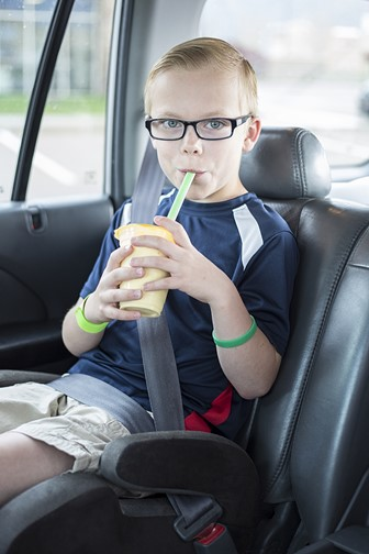 little boy sitting on a booster seat drinking a smoothie while wearing a seatbelt