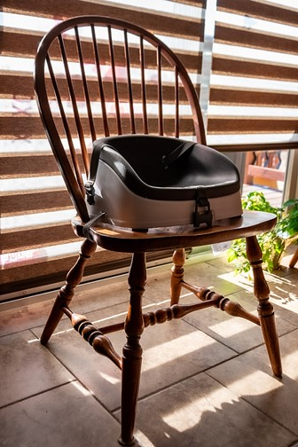 empty toddler booster seat on a wooden chair
